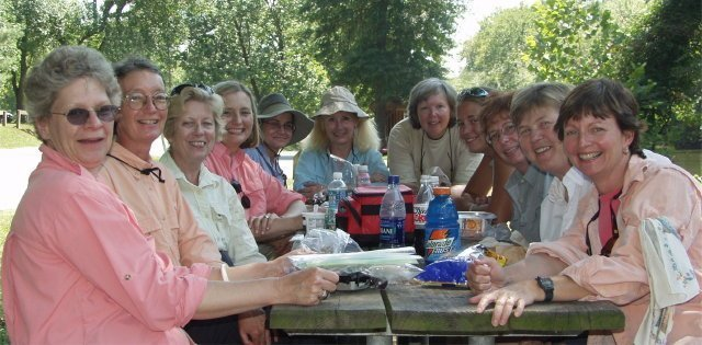 Chesapeake Women Anglers enjoying lunch under the trees on the bank of the Potomac River